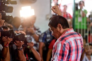 Rodrigo Duterte, Mayor of Davao and presidential candidate, gestures to members of the media at a polling station during the presidential election in Davao, Mindanao, the Philippines on Monday, May 9, 2016. Filipinos began voting in a holly contested presidential election that's seen Rodrigo Duterte, the controversial mayor of Davao City, propelled to the front of the pack with his tough talk to combat crime and deal with traffic-clogged roads in the Philippines. Photographer: Veejay Villafranca/Bloomberg via Getty Images